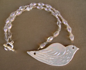 white dove clay pendant with mother of pearl on a beaded necklace